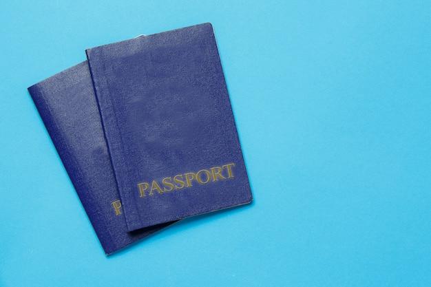 Passaportes de dois viajantes sobre fundo azul. conceito de viagens