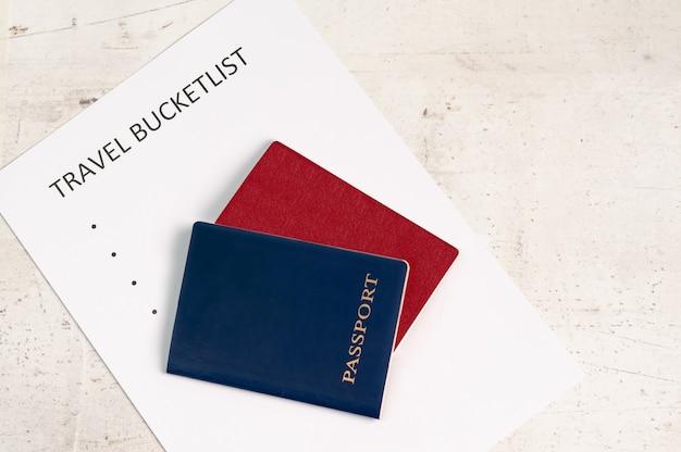 Passaportes de viagem azul e vermelho, ao lado da inscrição bucketlist de viagem