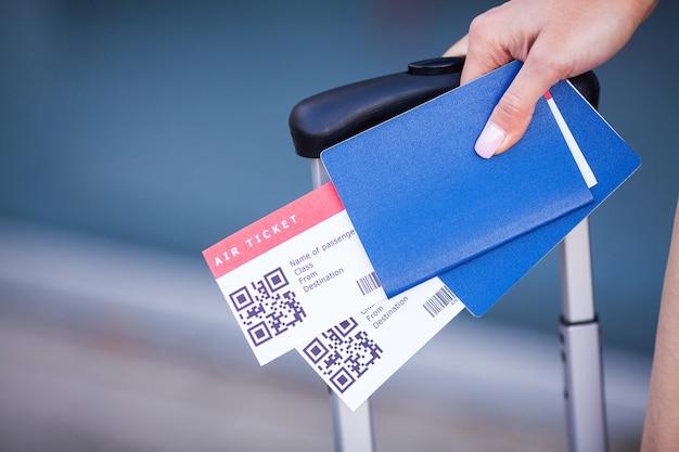Passaportes e bilhetes para o voo na mão da mulher