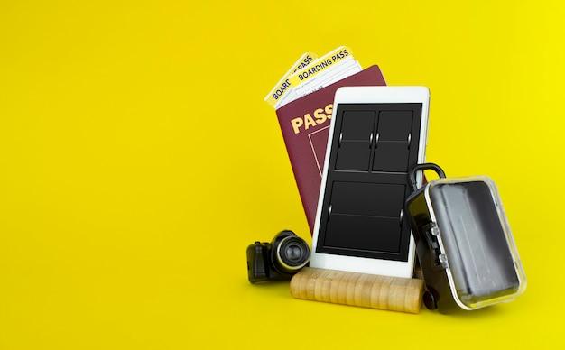 Passaportes e ingressos com mala em fundo amarelo.