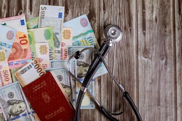 Passaportes húngaros de dinheiro notas de dólar dos eua e forints de notas húngaras com estetoscópio médico no hospital do consultório médico