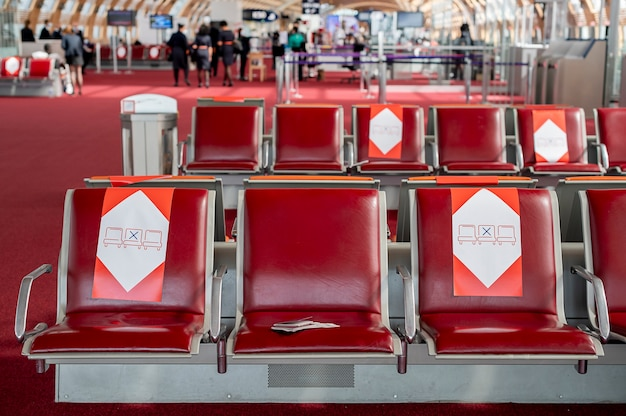 Passaportes repousam em uma cadeira na sala de espera na distância social do aeroporto