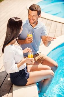 Passar algum tempo juntos na piscina. vista superior de um casal feliz em trajes casuais sentado à beira da piscina e conversando