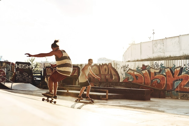 Passar bons momentos com os amigos. comprimento total de dois jovens andando de skate enquanto se divertem na pista de skate ao ar livre