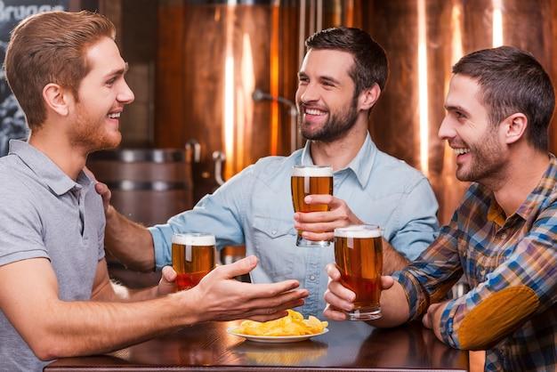 Passar bons momentos com os amigos. três jovens felizes em trajes casuais conversando e bebendo cerveja enquanto estão sentados em um bar de cerveja juntos