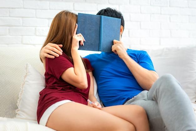 Passar bons momentos em casa. livro de leitura loving novo bonito dos pares e sorriso no sofá na sala de visitas em casa.