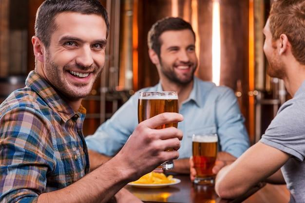Passar tempo com amigos. jovem bonito brindando com cerveja e sorrindo enquanto está sentado com os amigos em um bar de cerveja