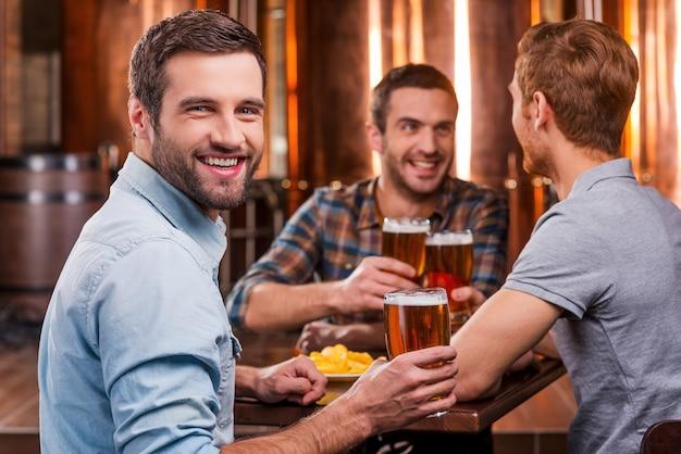 Passar tempo com melhores amigos. jovem bonito brindando com cerveja e sorrindo enquanto está sentado com os amigos em um bar de cerveja