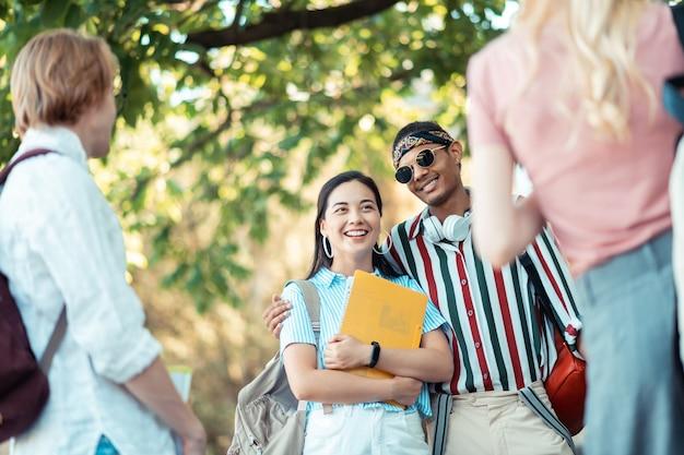 Passar tempo juntos. rapaz alegre, vestindo roupas brilhantes, abraçando sua namorada esperta com livros nas mãos e conversando com seus amigos.