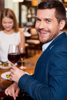 Passar um bom tempo no restaurante. jovem bonito segurando um copo com vinho tinto e sorrindo enquanto está sentado no restaurante com a namorada sentada ao fundo