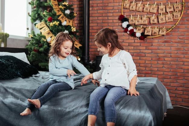 Passar um tempo brincando uns com os outros enquanto espera o natal. as crianças se sentam na cama. concepção de ano novo.
