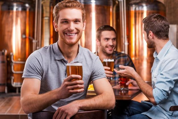 Passar um tempo em um bar de cerveja. jovem bonito brindando com cerveja e sorrindo enquanto seus amigos conversam ao fundo