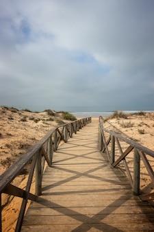 Passarela de madeira entre as dunas para ir à praia em chiclana