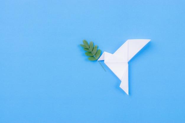 Pássaro branco feito de papel carregando galho de folha