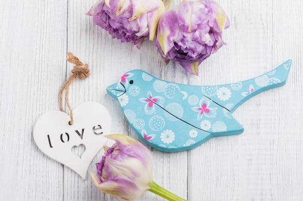 Pássaro de madeira azul com tulipas roxas e coração branco