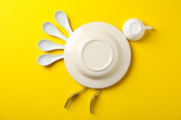 Pássaro feito de prato e talheres em fundo amarelo, vista superior