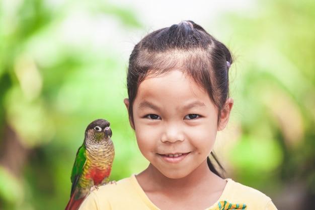 Pássaros papagaio lindo parado no ombro da criança. menina asiática criança brincar com seu pássaro papagaio de estimação