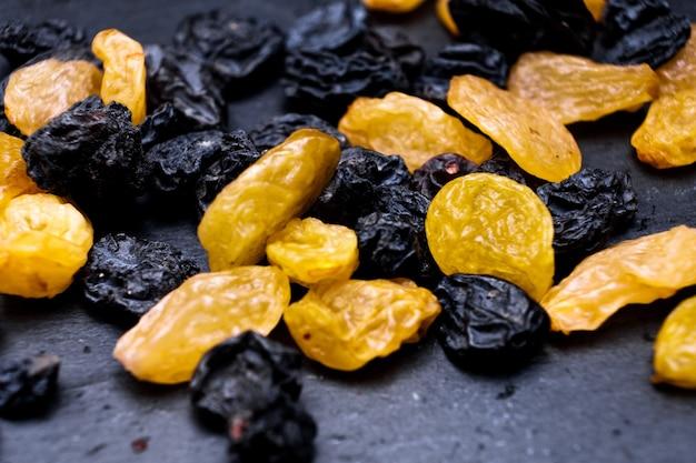 Passas, close-up de passas de passas amarelas, azuis, pretas, douradas sobre um fundo preto. vega food, macro foto