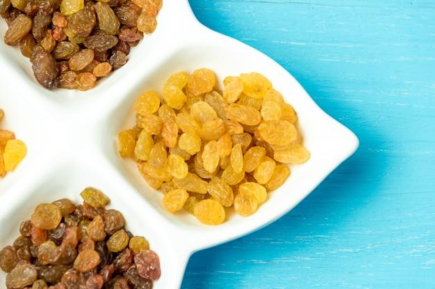 Passas douradas e marrons no prato. vista superior de uvas secas.