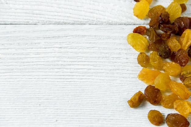 Passas douradas e marrons sobre fundo branco de madeira. vista superior de uvas secas com copyspace.