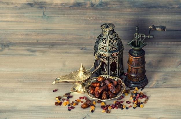 Passas e tâmaras em fundo de madeira. lanterna oriental vintage e moinho. imagem em tons de estilo retro