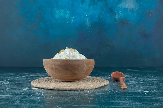 Passas em uma tigela de pudim de arroz ao lado da colher, sobre o fundo azul. foto de alta qualidade