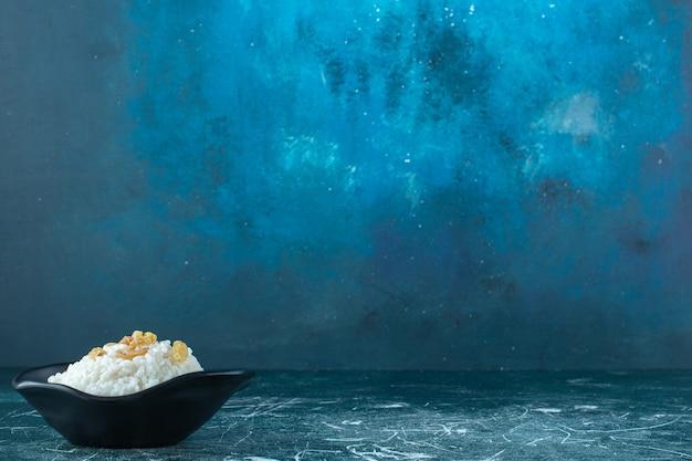 Passas em uma tigela de pudim de arroz, sobre o fundo azul. foto de alta qualidade