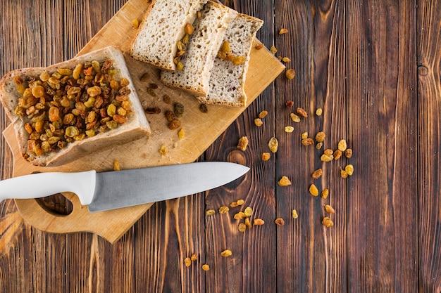 Passas nas fatias de pão com uma faca afiada na tábua sobre a mesa de madeira