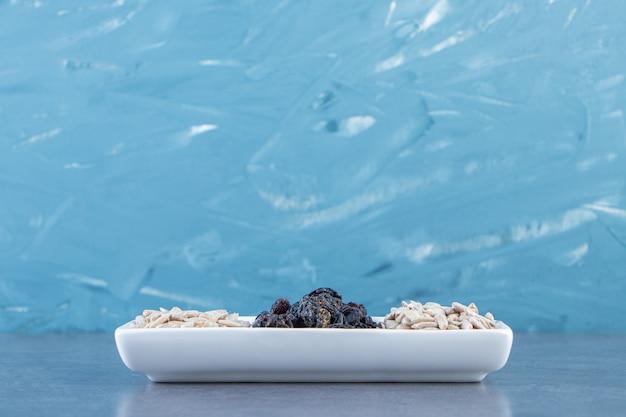 Passas pretas e sementes descascadas em um prato na superfície de mármore