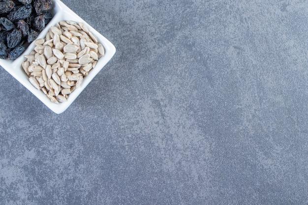 Passas pretas e sementes descascadas em um prato, no fundo de mármore.