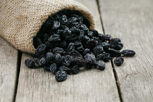 Passas pretas no saco de estopa sobre a mesa cinza de madeira