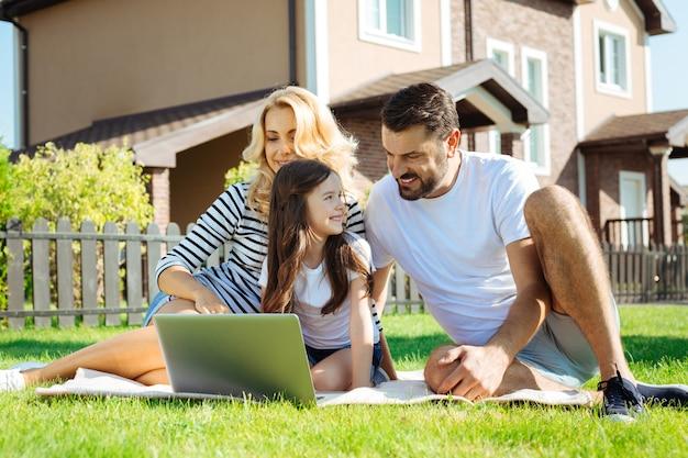 Passatempo agradável. jovens pais amorosos e sua filha sentados no tapete no quintal perto de sua casa e assistindo desenhos animados juntos no laptop
