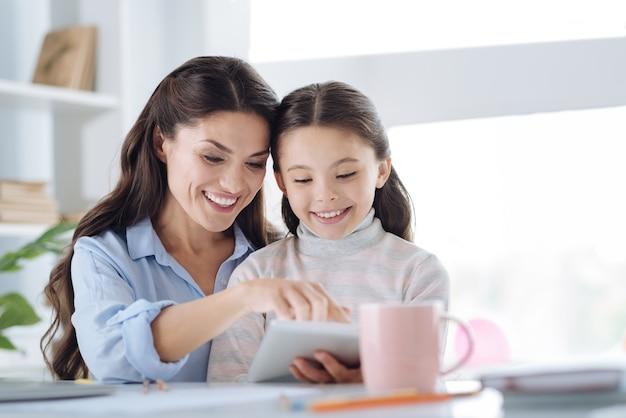 Passatempo agradável. mulher bonita e feliz sorrindo e lendo um livro com sua filha enquanto passa um tempo com ela