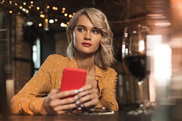 Passatempo agradável. mulher jovem e bonita sentada em um bar, mandando mensagem de texto para a amiga, depois de pedir uma taça de vinho