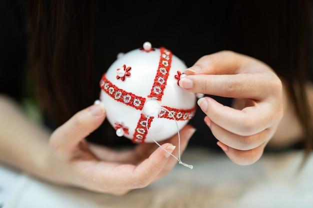 Passatempo criativo diy. fazendo artesanato artesanal branco elegantes bolas de natal com laço.