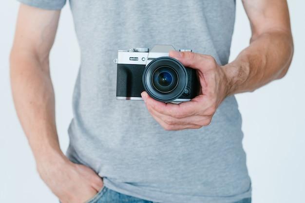 Passatempo criativo e lazer inspirado. homem irreconhecível, segurando a câmera fotográfica nas mãos.