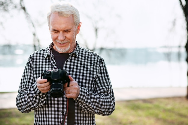 Passatempo criativo. homem feliz sênior posando no fundo desfocado e usando a câmera