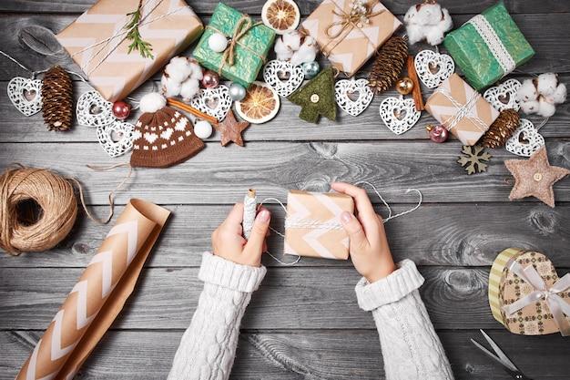 Passatempo criativo. presentes de natal com ferramentas e decorações. embalagem apresenta na mesa de madeira, vista superior.