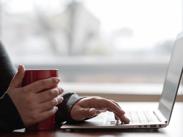 Passatempo de fim de semana ou dia de folga. mulher relaxada sentada perto do laptop do computador e segurando uma xícara. menina lendo as notícias, atualizando o perfil nas redes sociais ou apenas navegando