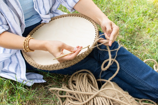 Passatempo de trabalho manual mulher está fazendo uma cesta de crochê agulha de crochê dourada cesta de juta para a decoração da casa