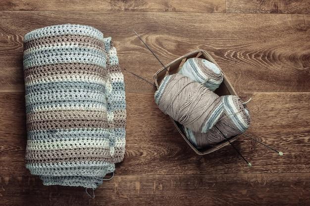 Passatempo doméstico. novelos de fios de lã, fios, produtos de malha no chão. vista do topo