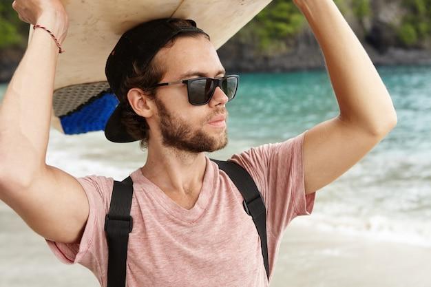 Passatempo e férias. jovem bonito com barba de óculos elegantes e snapback segurando a prancha sobre a cabeça, olhando para o oceano, esperando por grandes ondas