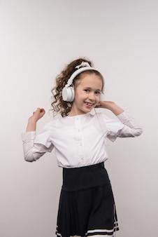 Passatempo favorito. linda garota encantada sorrindo enquanto ouve música