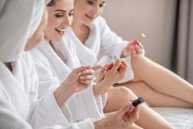 Passatempo favorito. três amigas adultas entusiasmadas em roupões de banho brancos e toalhas conversando olhando esmalte no spa