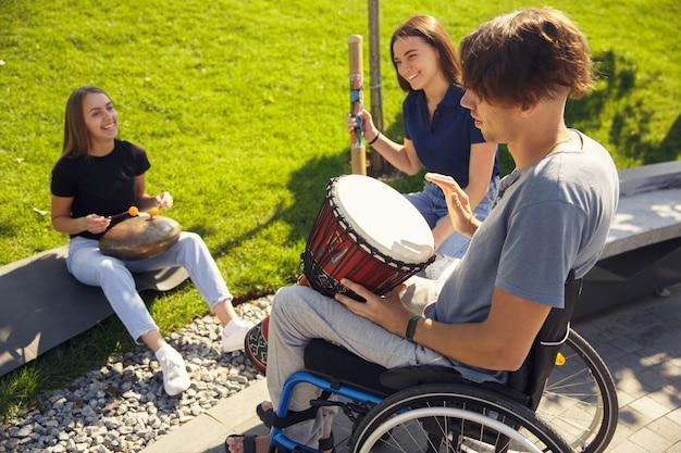 Passatempo. feliz homem deficiente em uma cadeira de rodas, passando um tempo com amigos tocando música instrumental ao vivo ao ar livre. conceito de vida social, amizade, possibilidades, inclusão, diversidade.