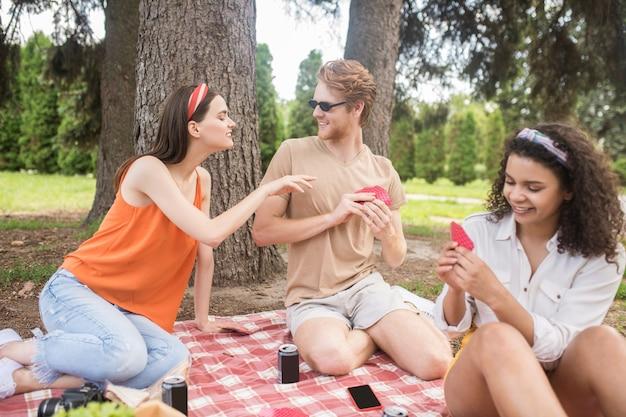 Passatempo, jogo. jovem ruivo alegre e duas garotas sorridentes e cabeludas jogando cartas na natureza em um dia bom