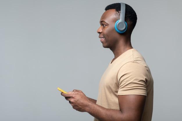 Passatempo, ouvir. jovem sorridente de pele escura com smartphone usando fones de ouvido sem fio em pé de lado, ouvindo alegremente