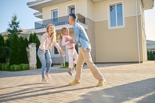 Passatempo. pai e mãe de meia-idade alegres brincando energicamente com a filhinha em frente a casa na rua em um dia ensolarado