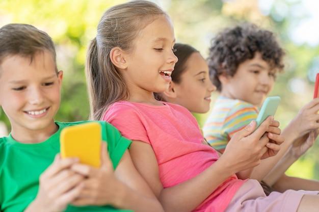Passatempo, smartphone. menina bonita loira entusiasmada olhando para um smartphone e amigos passando momentos de lazer juntos na natureza