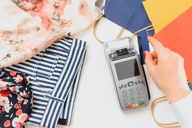 Passe mão com cartão de crédito através do terminal à venda no supermercado